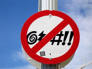 """a """"no cursing"""" sign on a post outdoors"""
