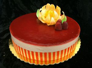 a vibrant mousse cake with a glaze and topped with a chocolate flower