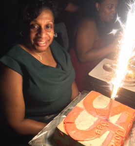 blog author neffi mom smiling over 55 birthday cake with sparkler candle in it