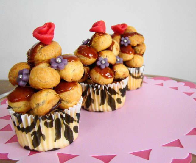 a small tower of mini cream puffs on a cupcake