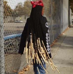 woman walking down street with floor length beaded braids