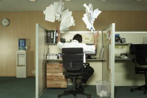 man sitting at desk throwing papers off desk in the air backward