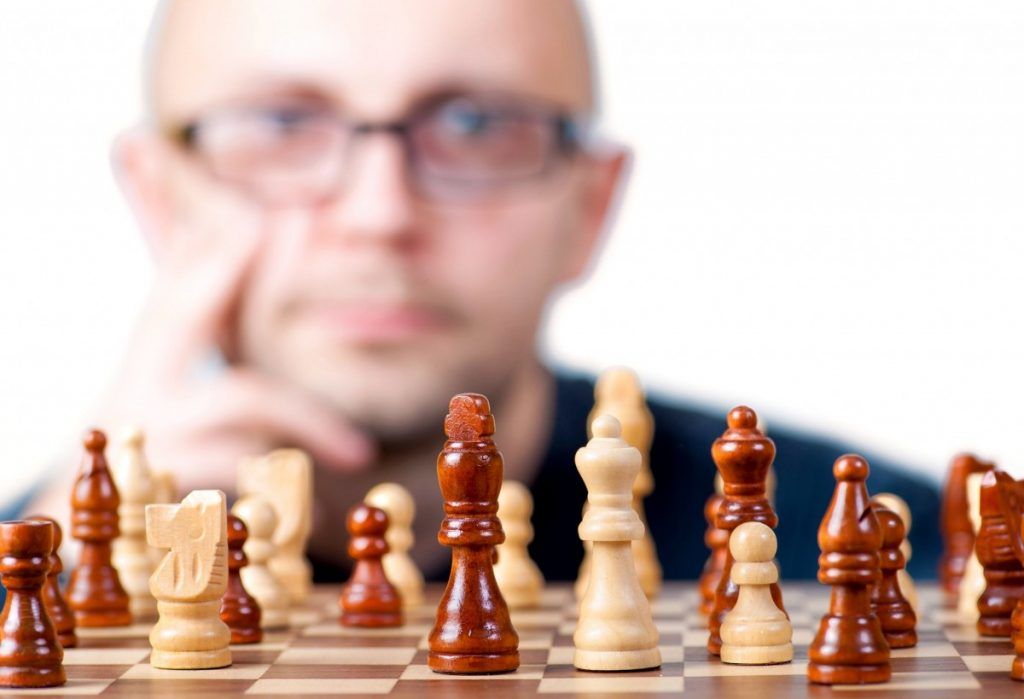 a man blurred in the background looking at a chessboard in focus in the foreground