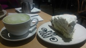 a decorated plate of pie and a mug filled with green tea