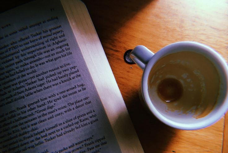 book with empty cup of coffee