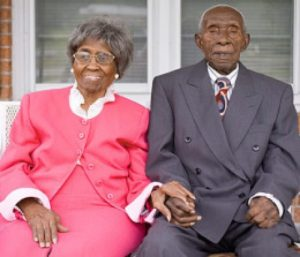older couple sitting holding hands