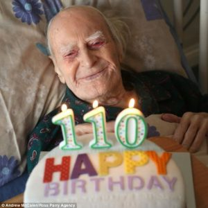 110 year old man being presented with a birthday cake