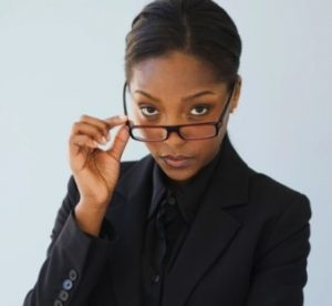 woman looking into camera holding glasses