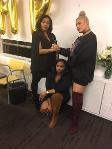 two women standing with another woman crouched between them
