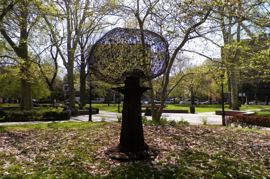 a sculpture in the midst of fallen leaves on the campus lawn