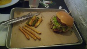 a stacked burger with fries on a metal pan
