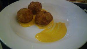 three fried pasta balls with sauce